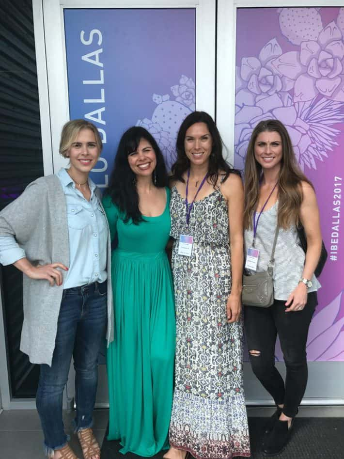 me, suzi, jeannie and amanda standing in front of the ibe dallas media wall