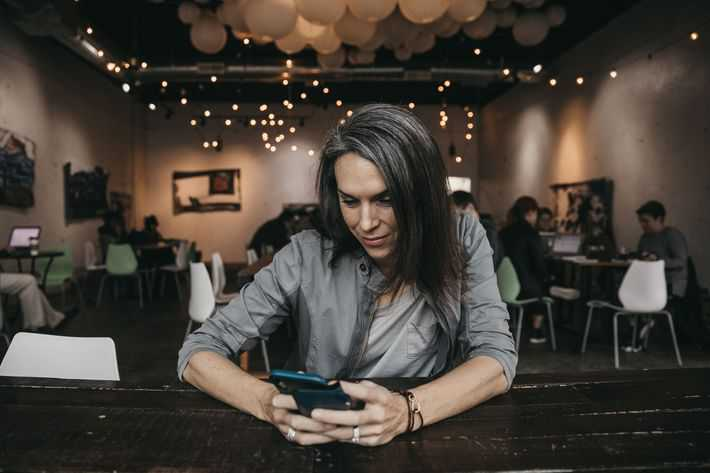 forty year old woman sitting in a coffee shop looking down at smartphone with the lighting showing her gray hair