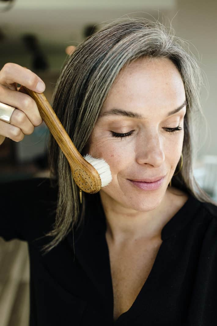 photo of Lisa running a dry brush up along her cheek