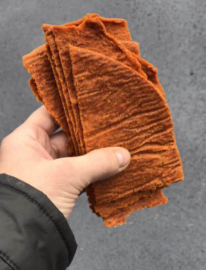 holding a stack of orange raw veggie bread