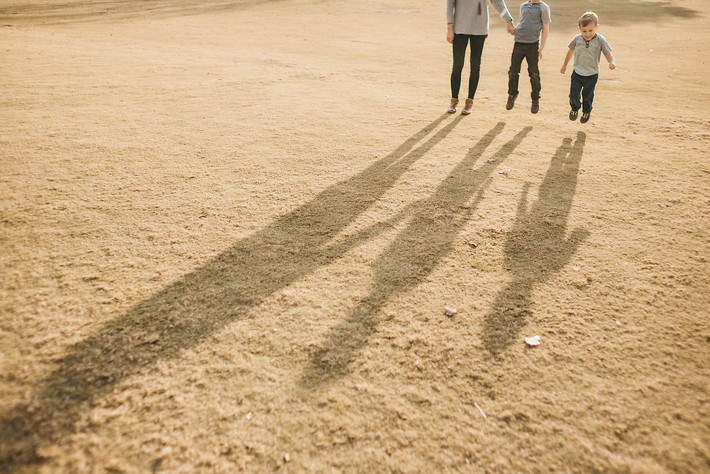 long shadows, a mom and her boys jumping in the air