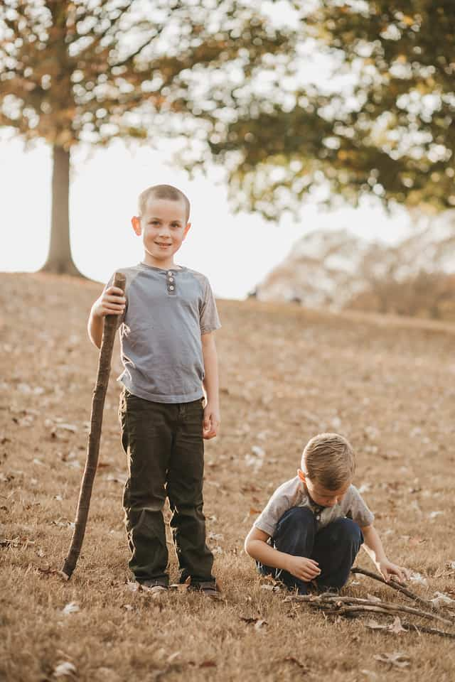 two boys playing with sticks on a hill