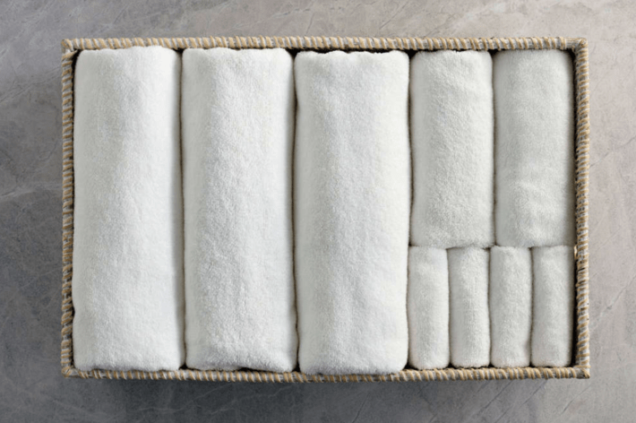 100% organic white cotton towels rolled in a basket