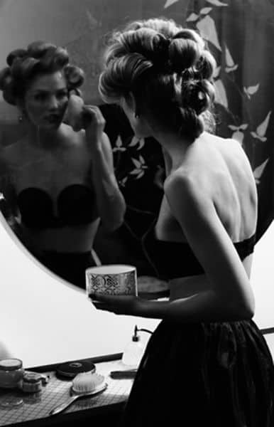 Black and white photo of a girl putting on makeup and getting ready to go out