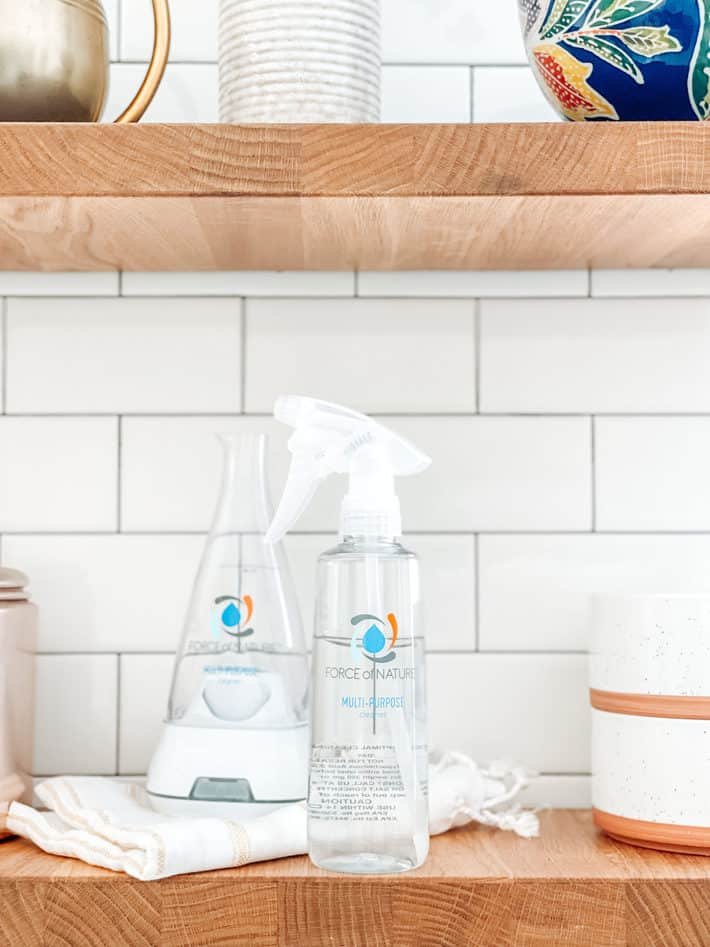 A clear spray bottle sits on a butcher block shelf next to terracotta bowls