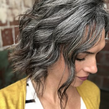 Photo of a woman who is growing her hair out to be gray. This photo shows what the hair color looks like 18 months into the graying process
