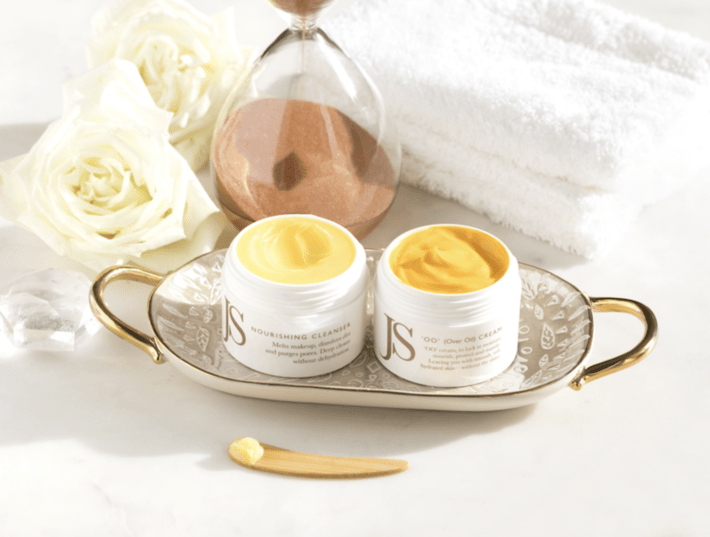 two containers of Jane Scrivner's OO Cream and Nourishing Cleanser laying on a plate