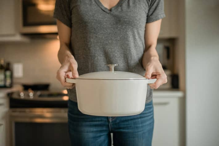 Torso shot of This Organic Girl standing in her kitchen holding a white MILO Dutch Oven in both hands