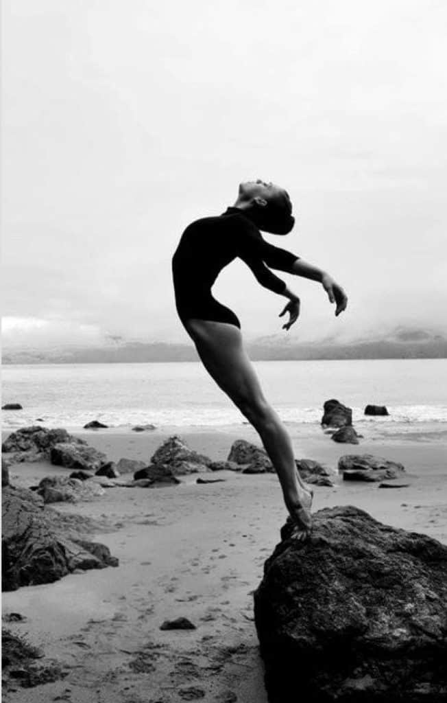 a black and white photograph of a dancer standing on a rock at the beach with her chest to the sky and her arms flung behind her