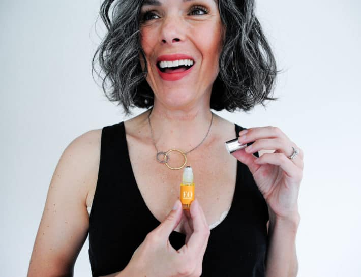 This Organic Girl laughing and holding the EO natural fragrance at her breast bone wearing a black tank against a white background