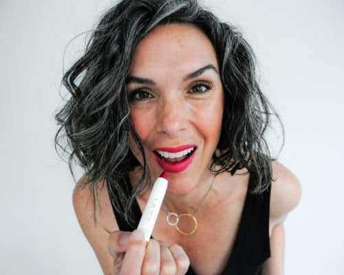 This Organic Girl applying OGEE Sculptured Lip Oil while looking into the camera wearing a black tank dress against a white background