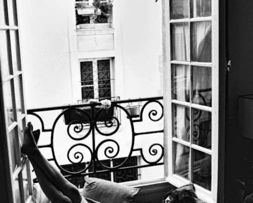 black and white photo of a girl reading a book by an open window