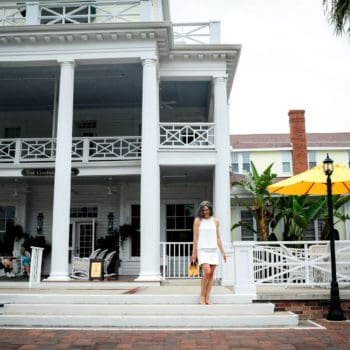 girl wearing a white shirt and white skirt and yellow shoes in front of a souther plantation