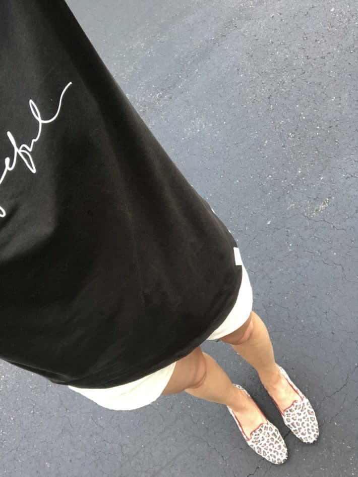 top down selfie of a black t-shirt, white shorts and rothy's animal print recycled plastic shoes