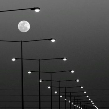 black and white photo of the sky with a full moon and street lights forming a path