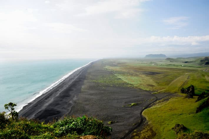 Dyrhólaey from the top looking down at the black sand beaches and forever skyline