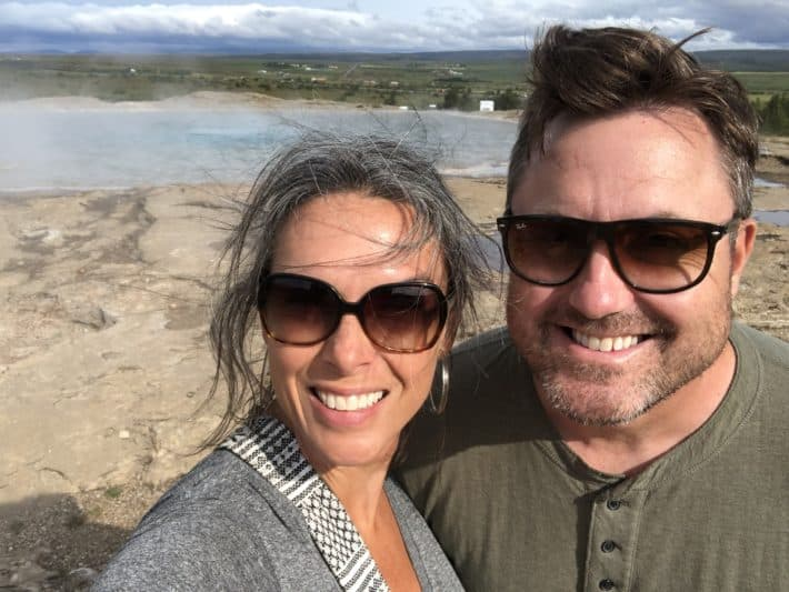 a couple standing in front of Geysir