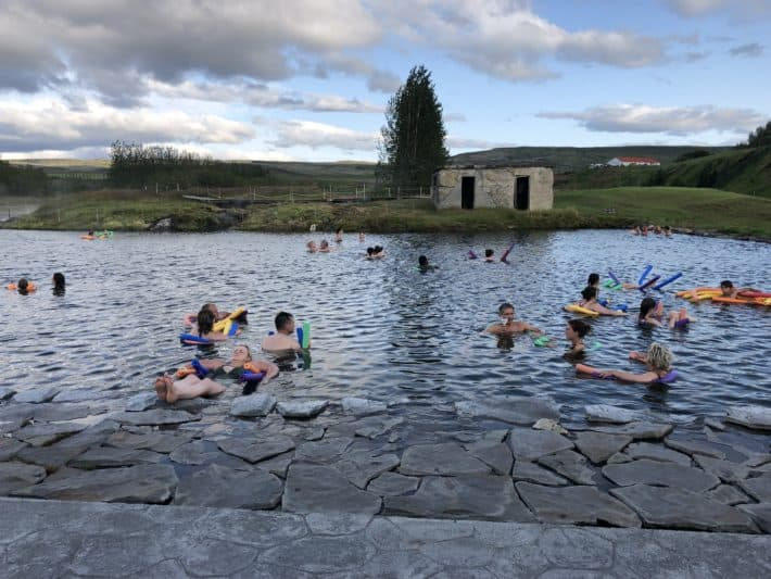 a bunch of people on noodles in a natural pool Iceland