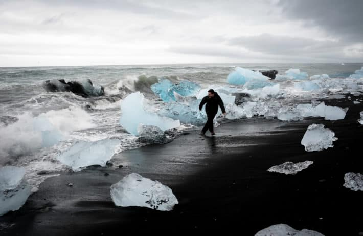 running away from the waves among icebergs at Diamond Beach Iceland