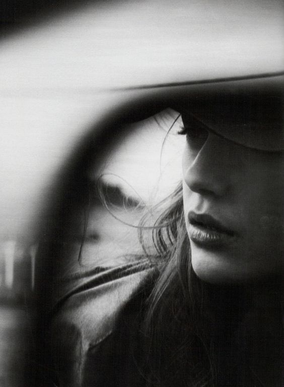 black and white photo of contemplative girl's reflection in a mirror