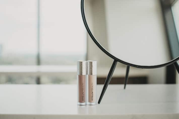 two Fitglow Beauty Lip Serums next to a mirror on a white counter