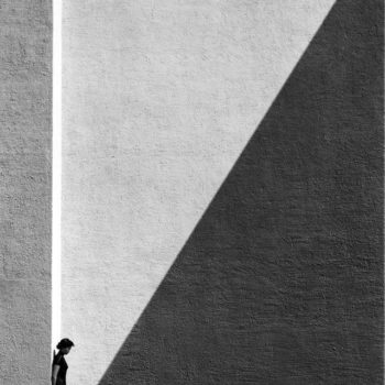 woman standing against a wall with a diagonal shadow that cuts the wall into half light and half dark