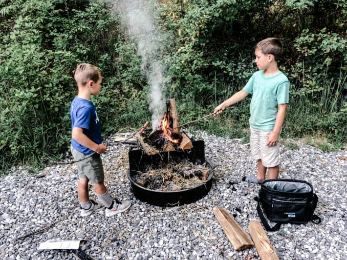 kids cooking hotdogs over an open fire in the woods