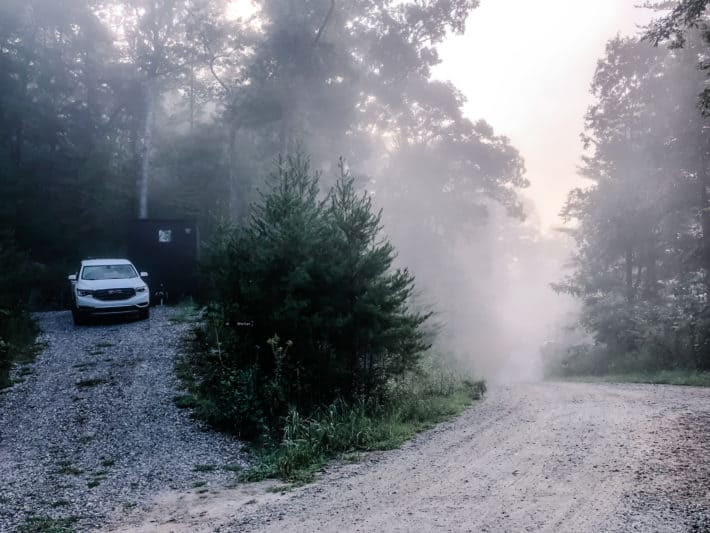 the morning fog overtaking a Getaway cabin and the dirt road