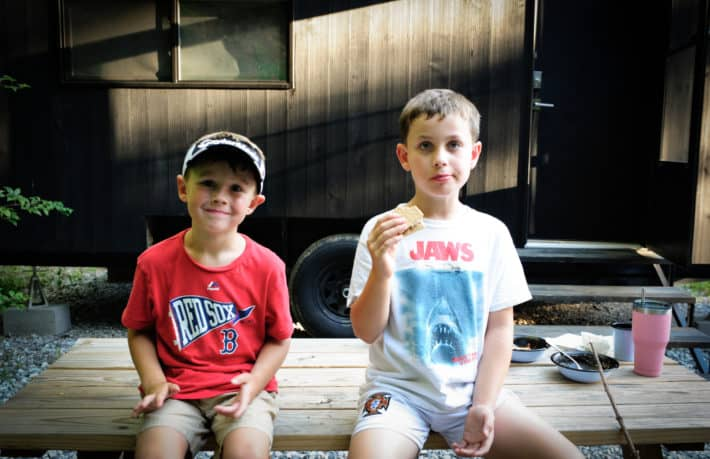 two boys siting on a picnic table eating smores