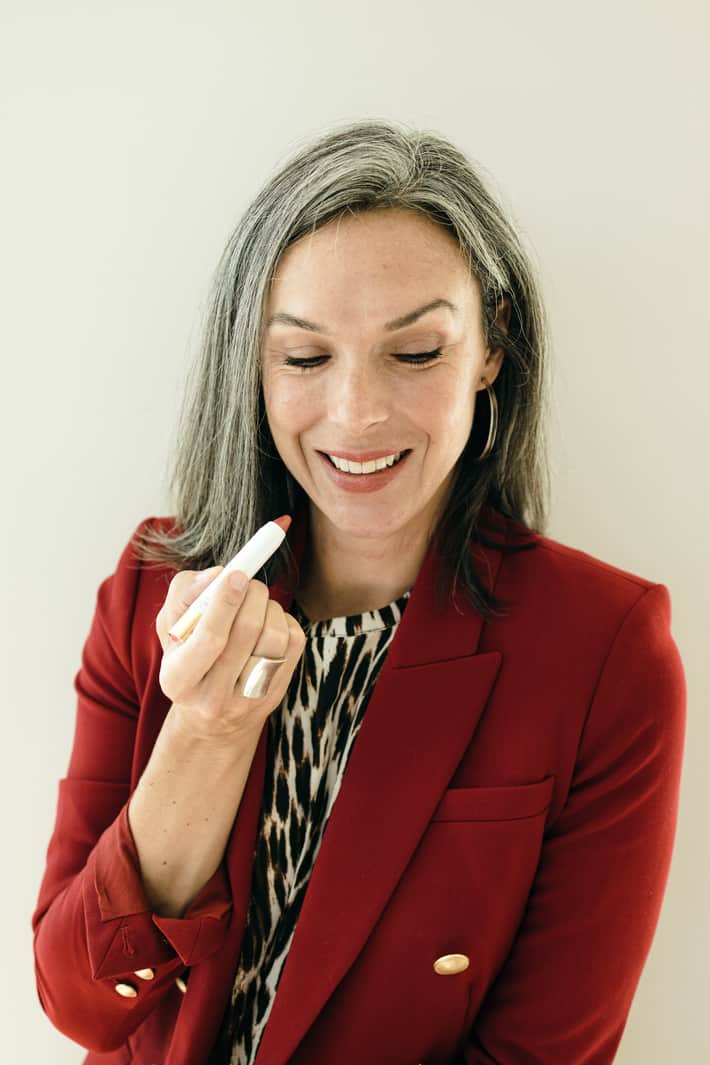 Lisa applies a rose-nude colored tinted lip oil.