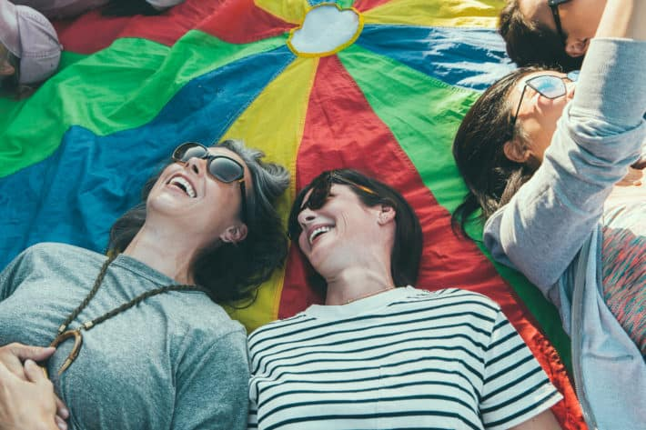 girlfriends laughing and laying on a parachute