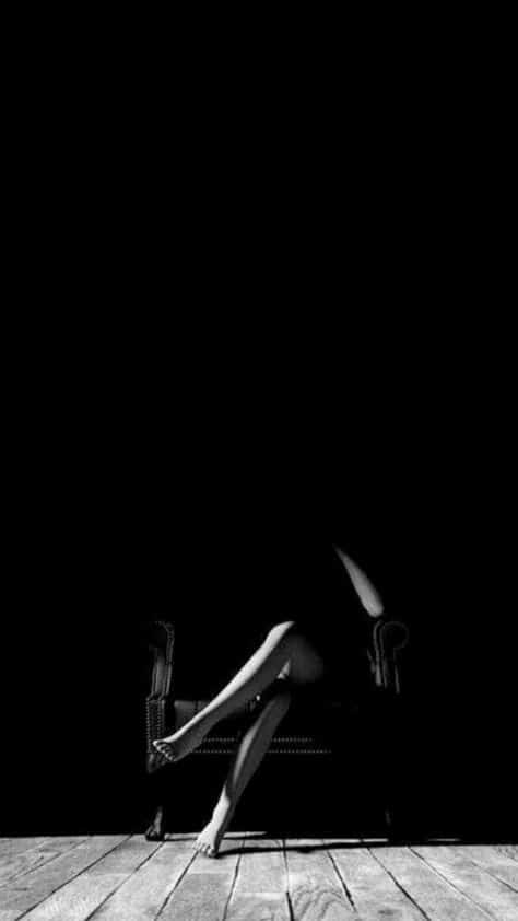 black and white photo illuminating legs sitting in a chair
