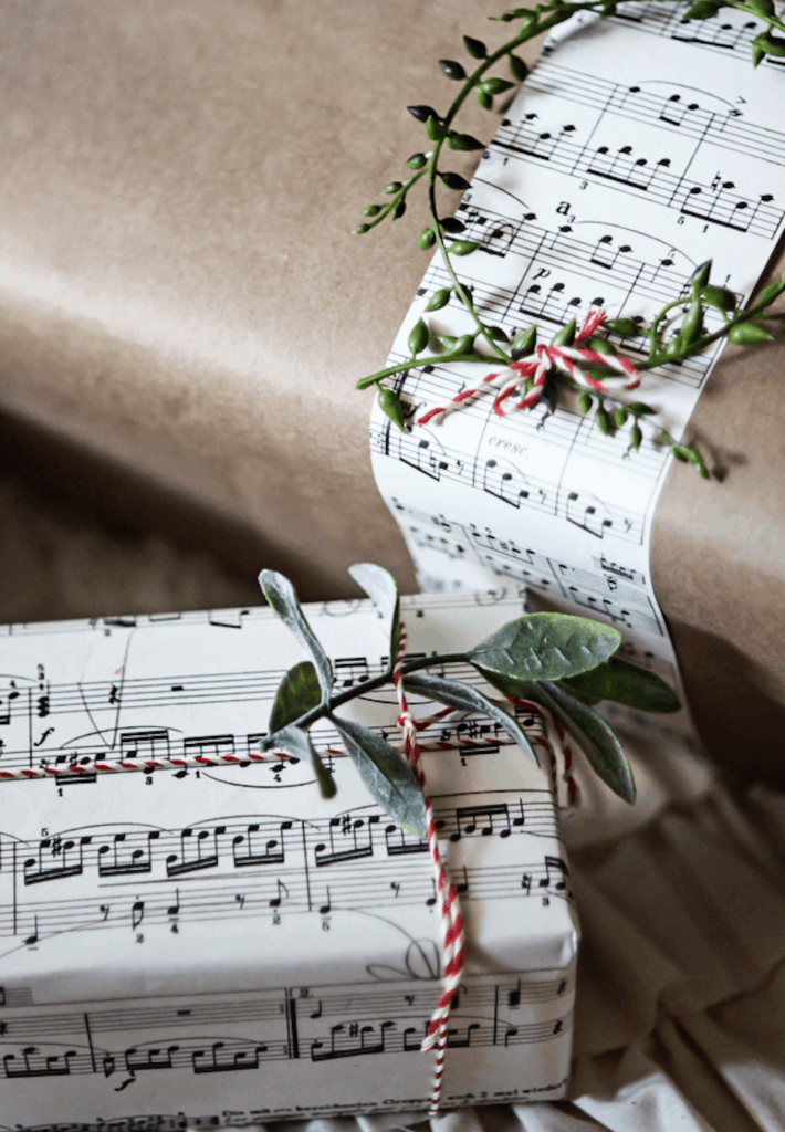 two gifts wrapped in sheet music with berries and greenery