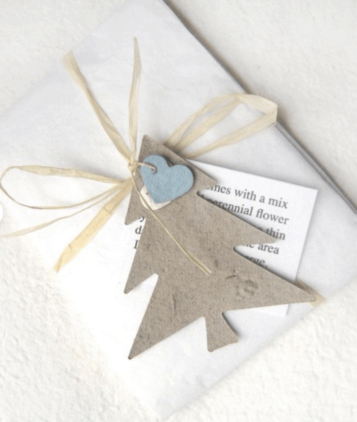 white gift adorned with seed paper cut in the shape of a tree