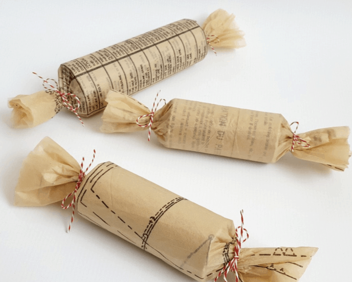 three tube size presents wrapped in sewing patterns