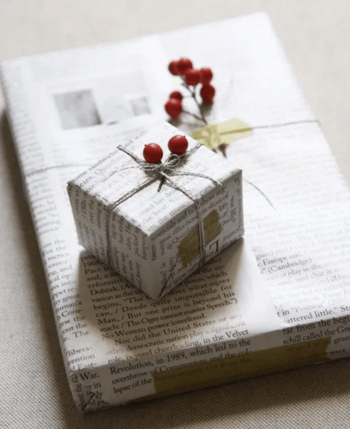 two gifts wrapped in newspaper adorned with red berries
