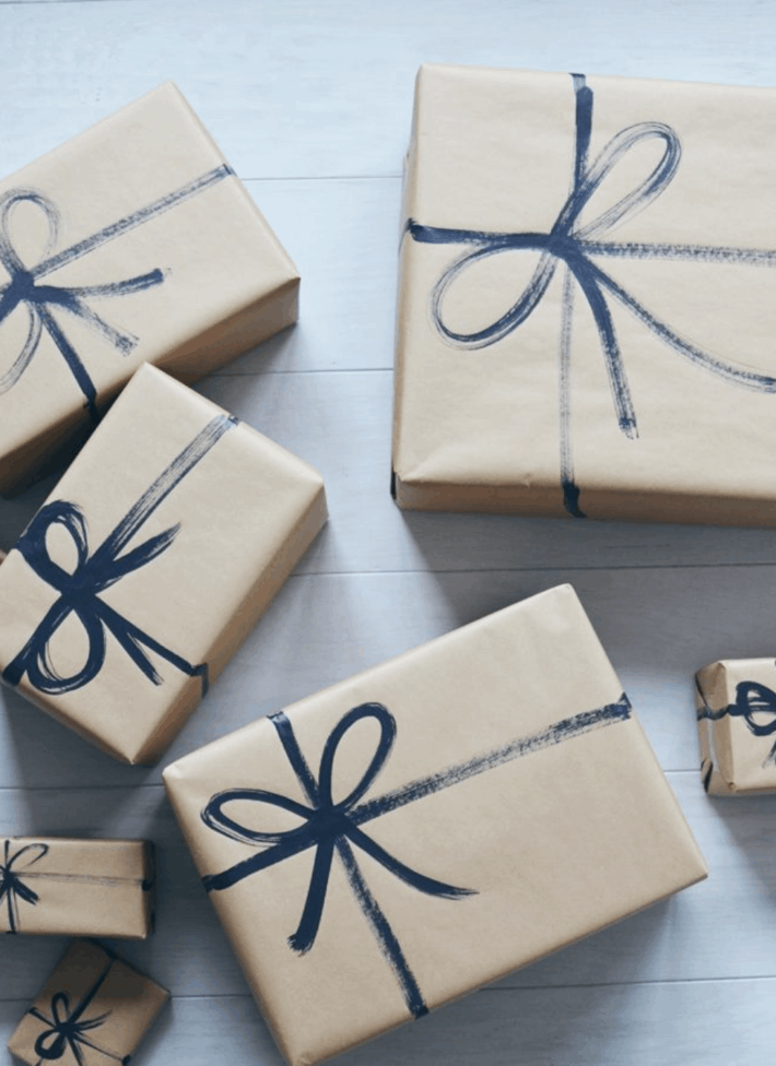several boxes wrapped in brown paper with a painted bow
