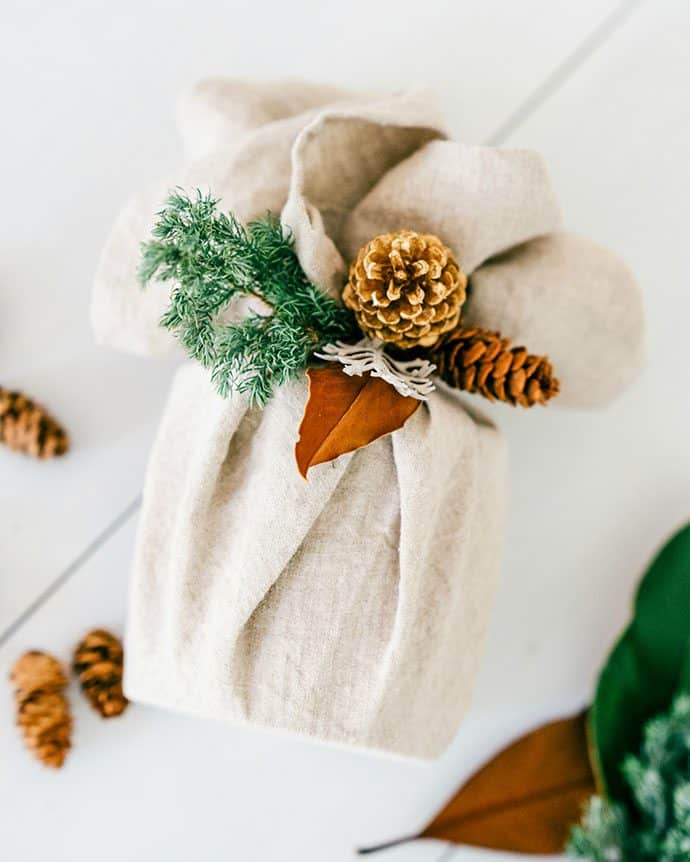 gift wrapped in white fabric with pine cones and greenery