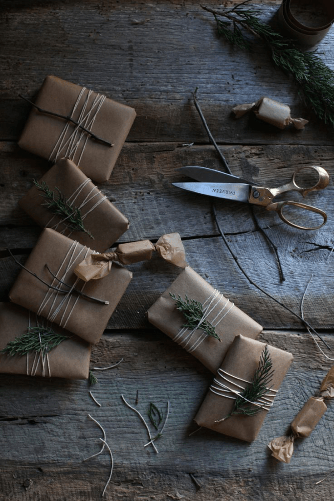several gifts wrapped multiple times in twine and adorned with live foliage