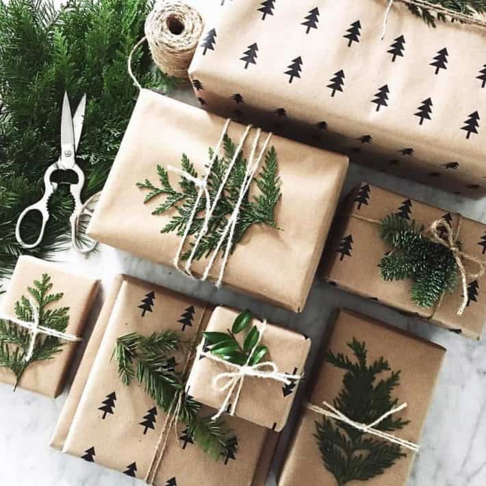 several gifts wrapped in brown paper, twine, foliage and stamped pine trees