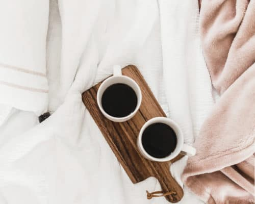 two coffee cups on a plank