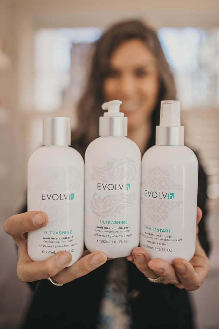 Lisa holding three bottles of EVOLVh haircare products