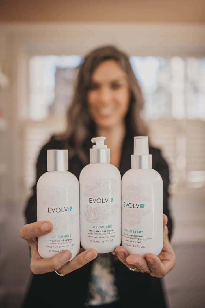 Lisa holding three EVOLVh products in her hands, showing shampoo, conditioner, and leave-in conditioner