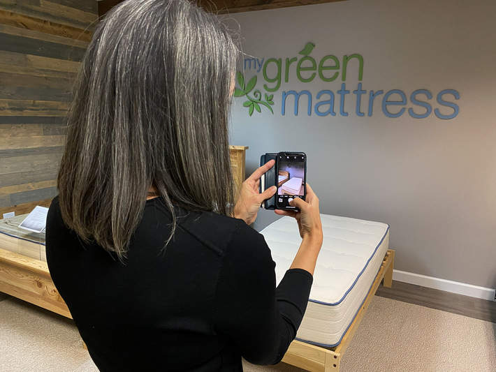 me taking a photo of a my green mattress in the showroom