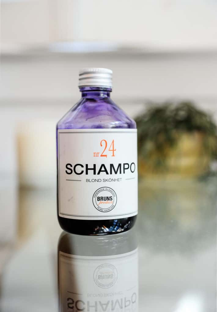 Bruns SCHAMPO N24 shampoo bottle sitting on a glass table