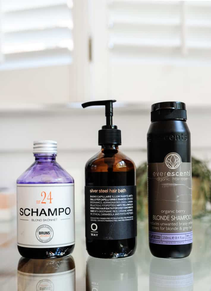 3 bottles of purple shampoo with labels and logos showing on a glass table