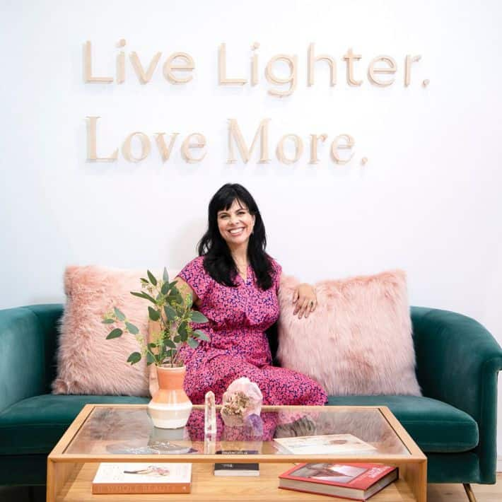 "Jeannie sitting on a green couch with wall decor behind her reading ""Live Lighter. Love More."""