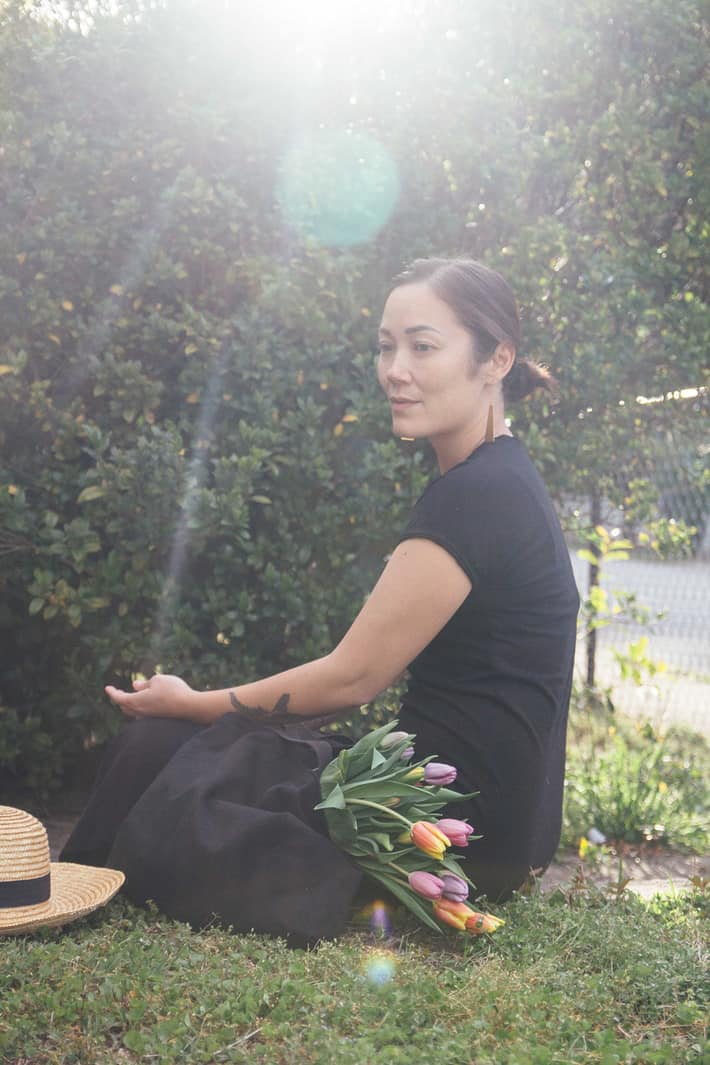 Tanya sitting in her yard while wearing the black maxi dress with a bouquet of flowers next to her