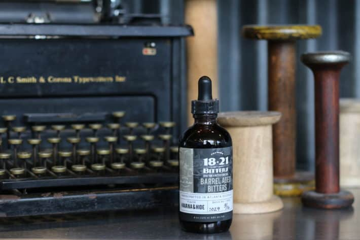 bottle of 1821 bitters on a table with typewriter in foreground