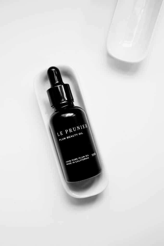 Le Prunier flat lay black bottle on a white background